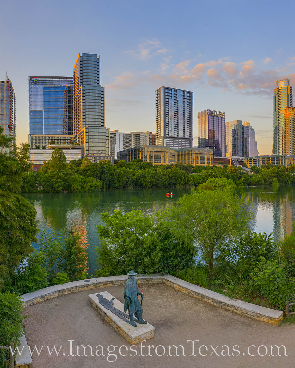 Along the hike and bike path of Town Lake (Ladybird Lake) the statue memorializing Stevie Ray Vaughan stands in the shadown of...
