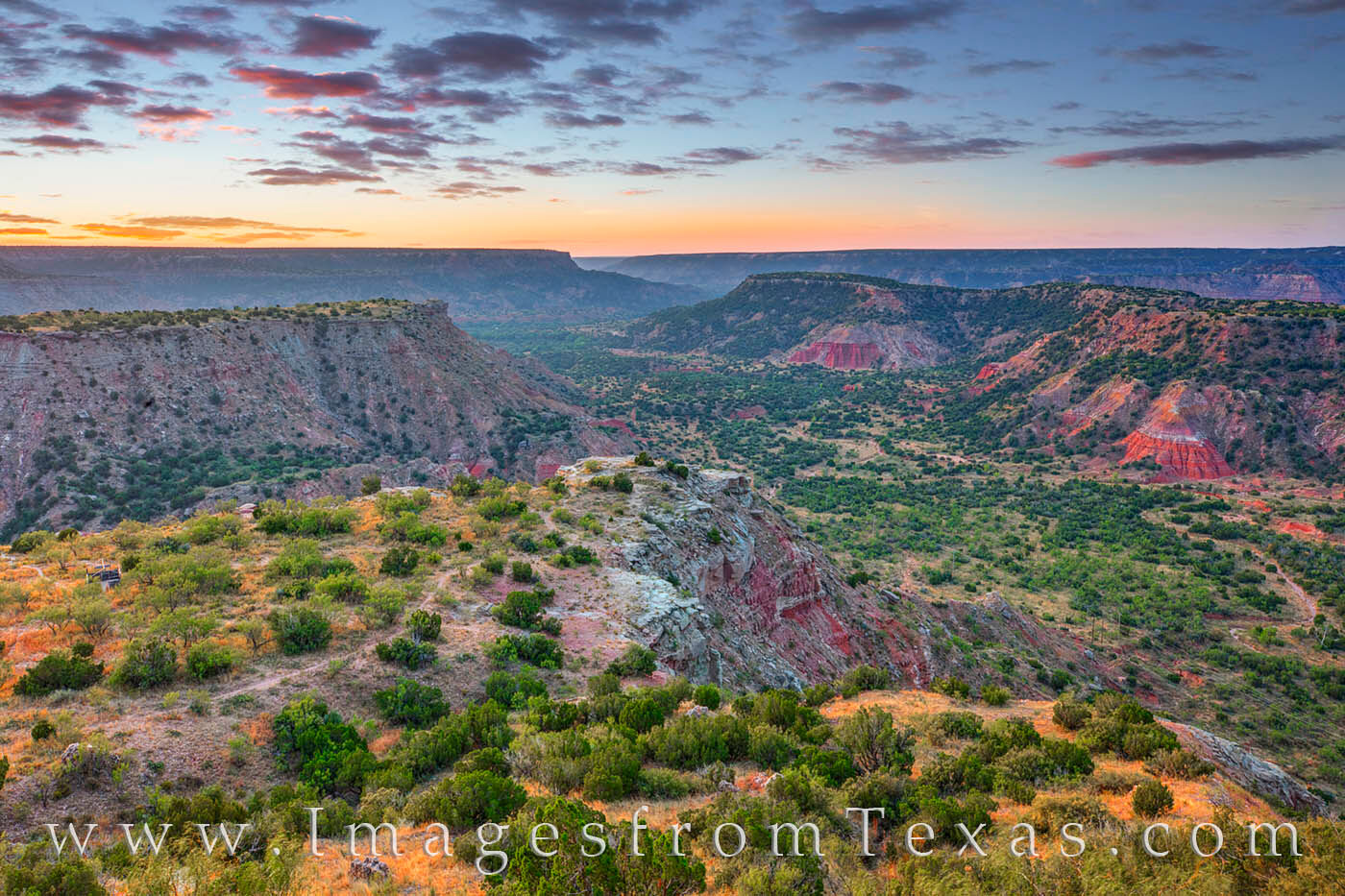 From the rim of the second largest canyon in the U.S., Palo Duro Canyon begins to show its colors under a colorful and tranquil...