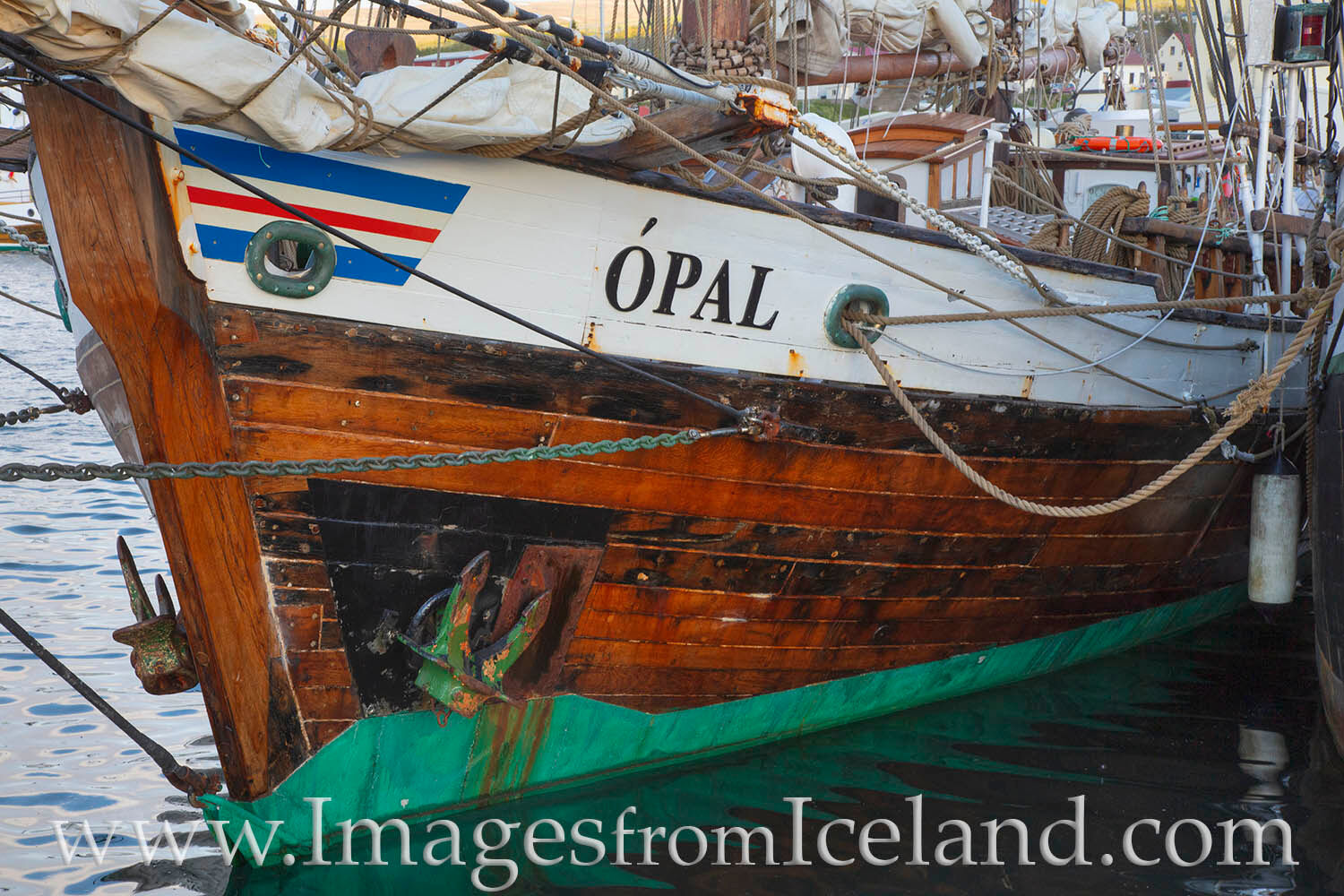 A ship called the Opal rests in the quiet harbor of Husavik, Iceland.