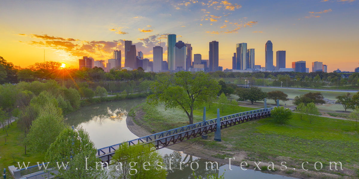 From just above Buffalo Bayou, the Houston skyline is seen on a beautiful spring sunrise. Below, the Carruth Pedestrian bridge...