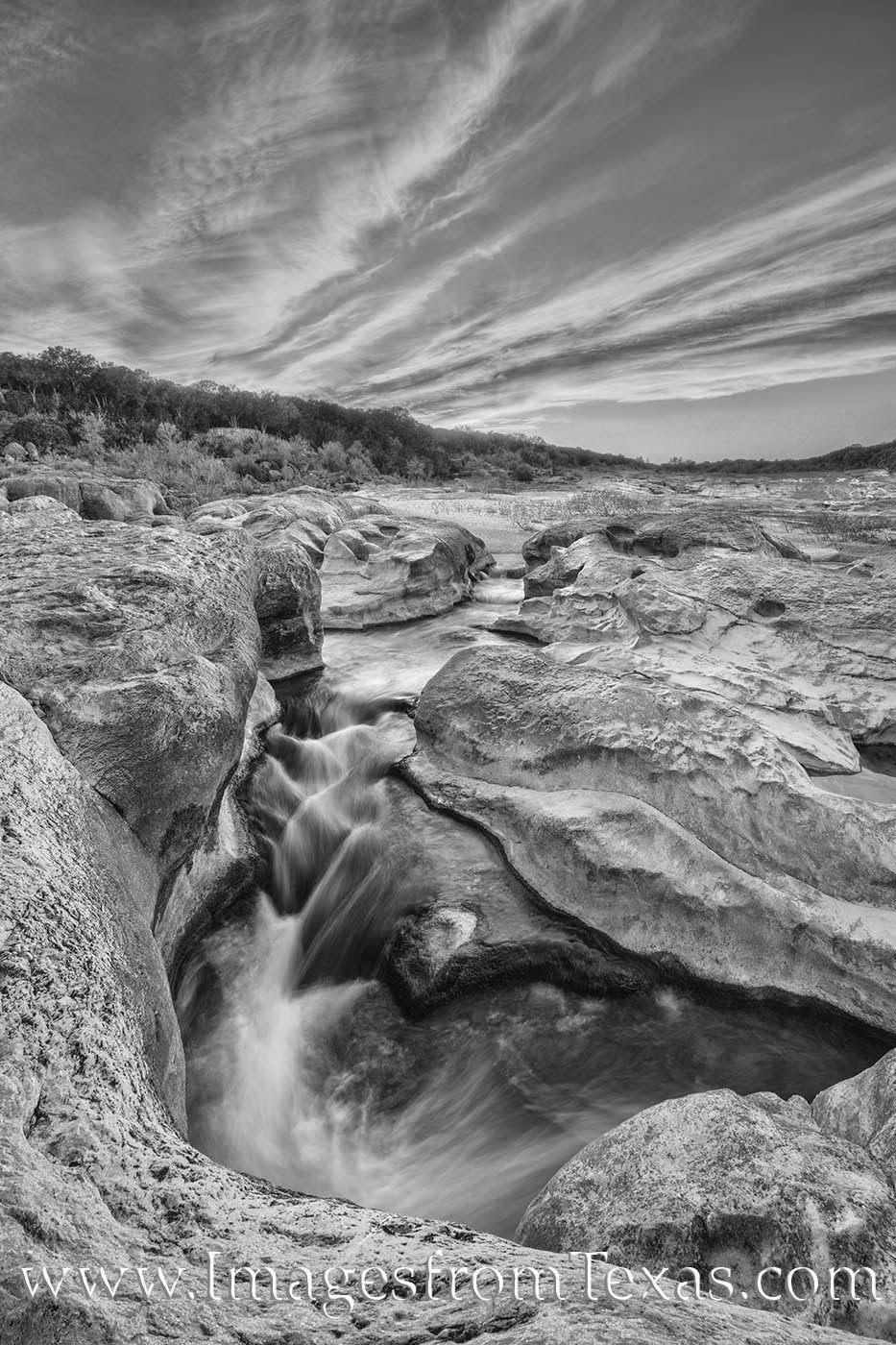 The cool waters of the Pedernales River flows through a small limestone canyon beneath a evening Spring sky in this black and...
