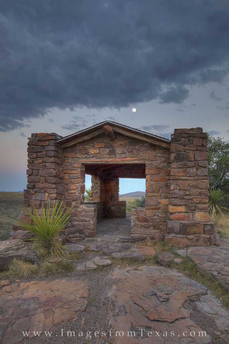 A full moon sets in the west over Davis Mountains State Park on a June morning. This old stone structure was built by the CCC...