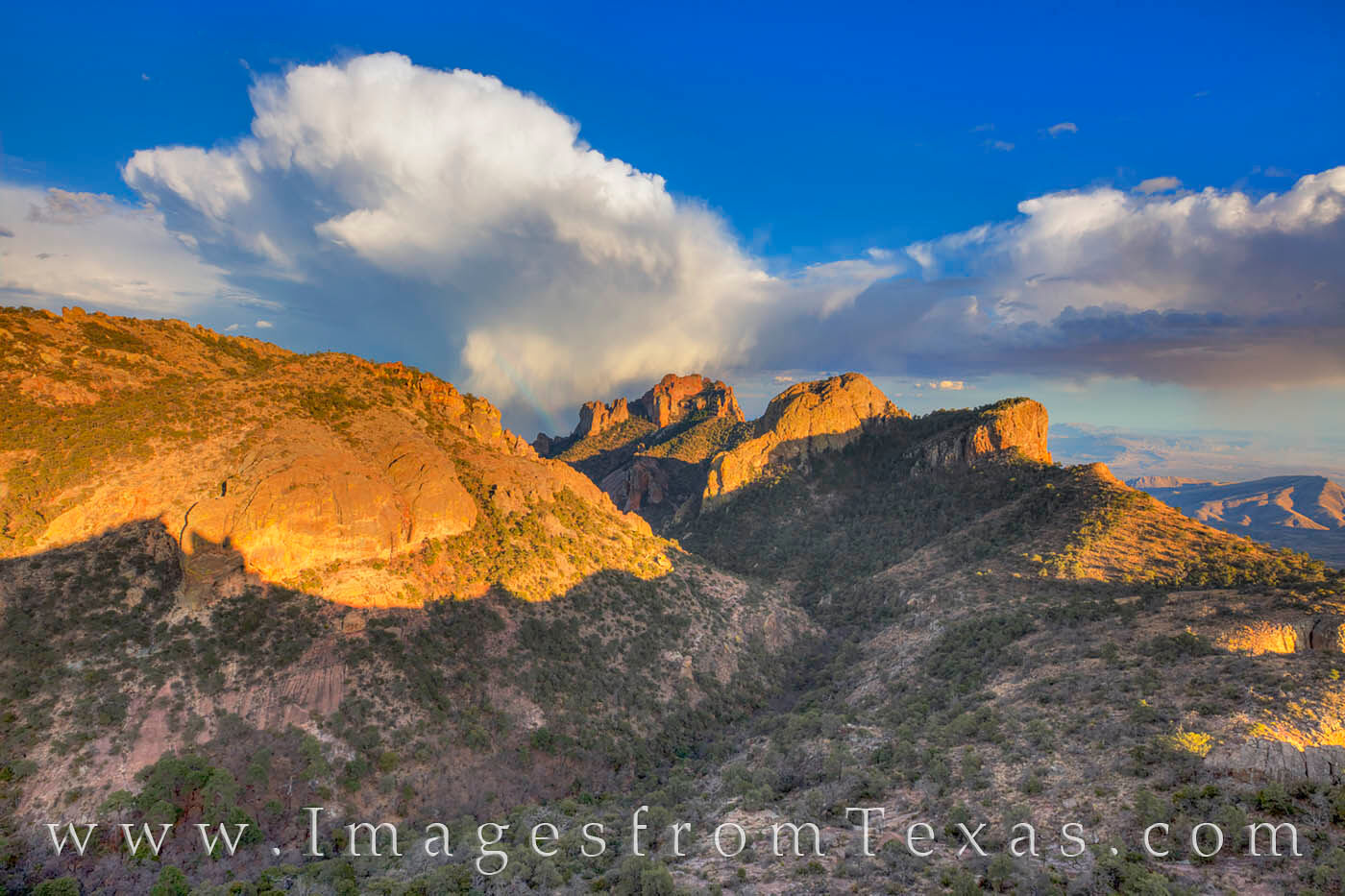 As storm clouds form over the Chisos Mountains, a rainbow forms as the sun begins to fall in the western horizon. This view of...