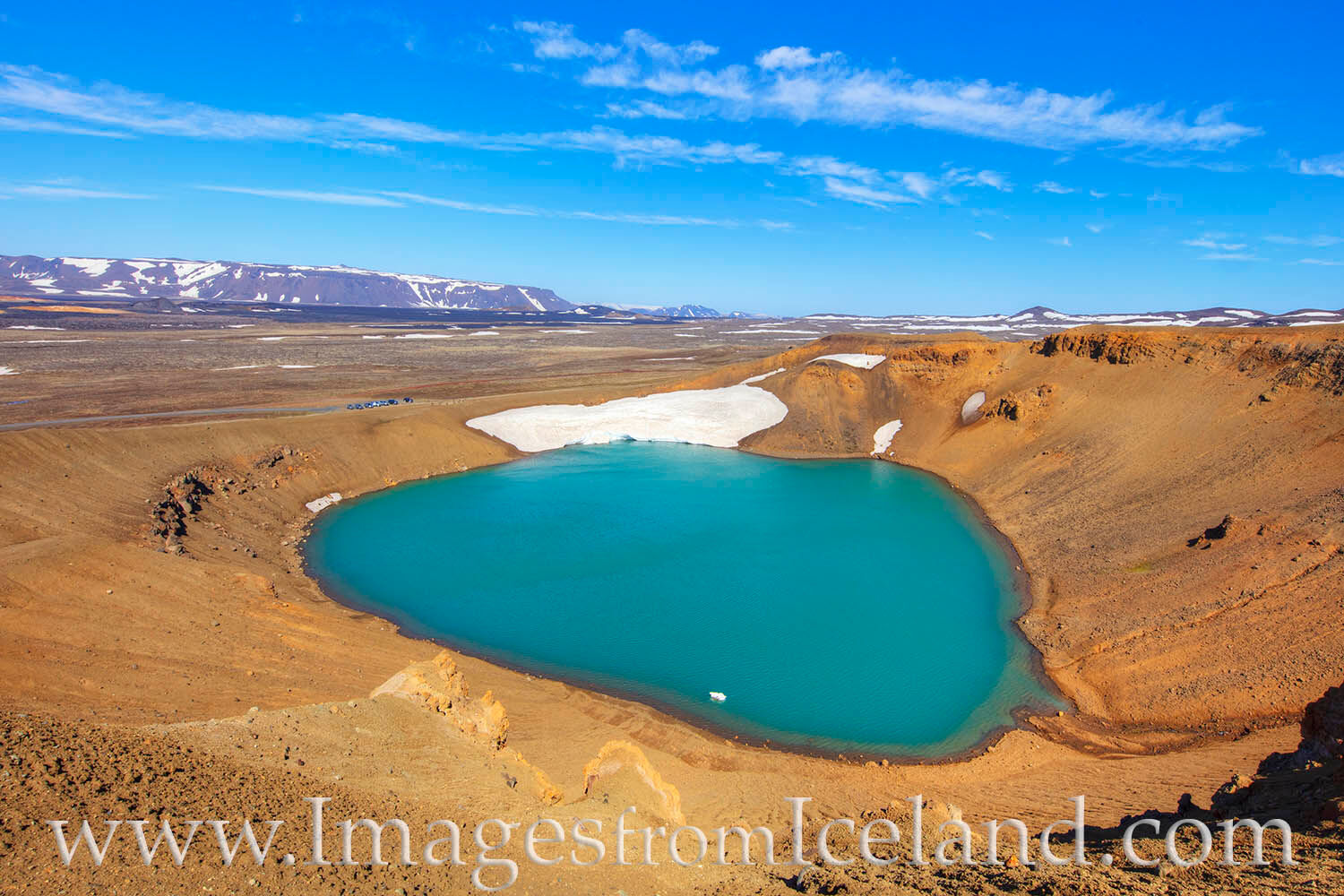 From high up on the rim of an old volcano, this view shows the amazing blue-green water of a lake at the bottom of the Stóra...