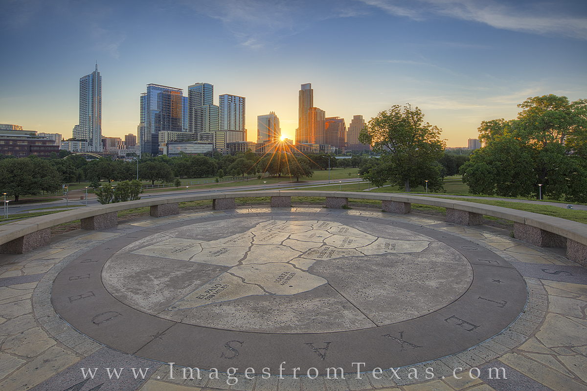 The Austin skyline rises into the cool springtime morning at sunrise. In the foreground, the state of Texas is shown on the small...