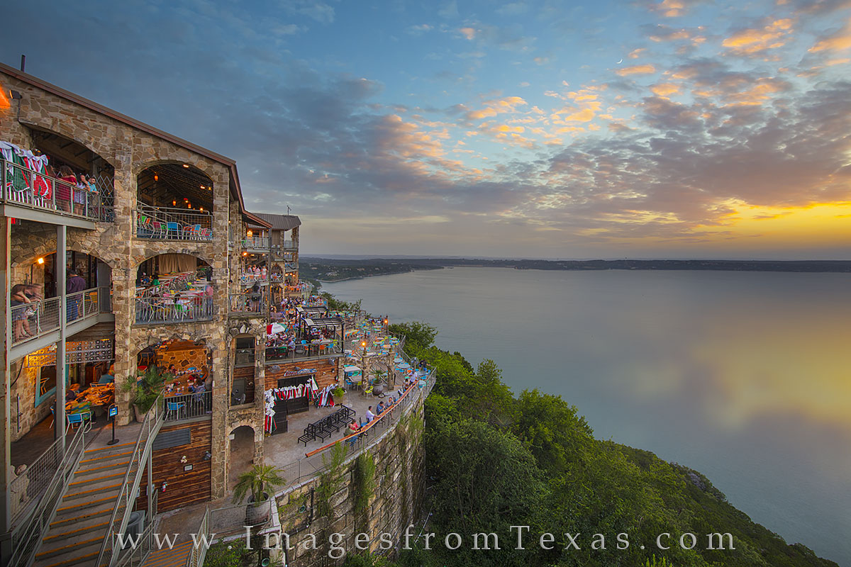 The last light of the sun lights up the western sky over Lake Travis and the Texas Hill Country. Patrons at the iconic Austin...