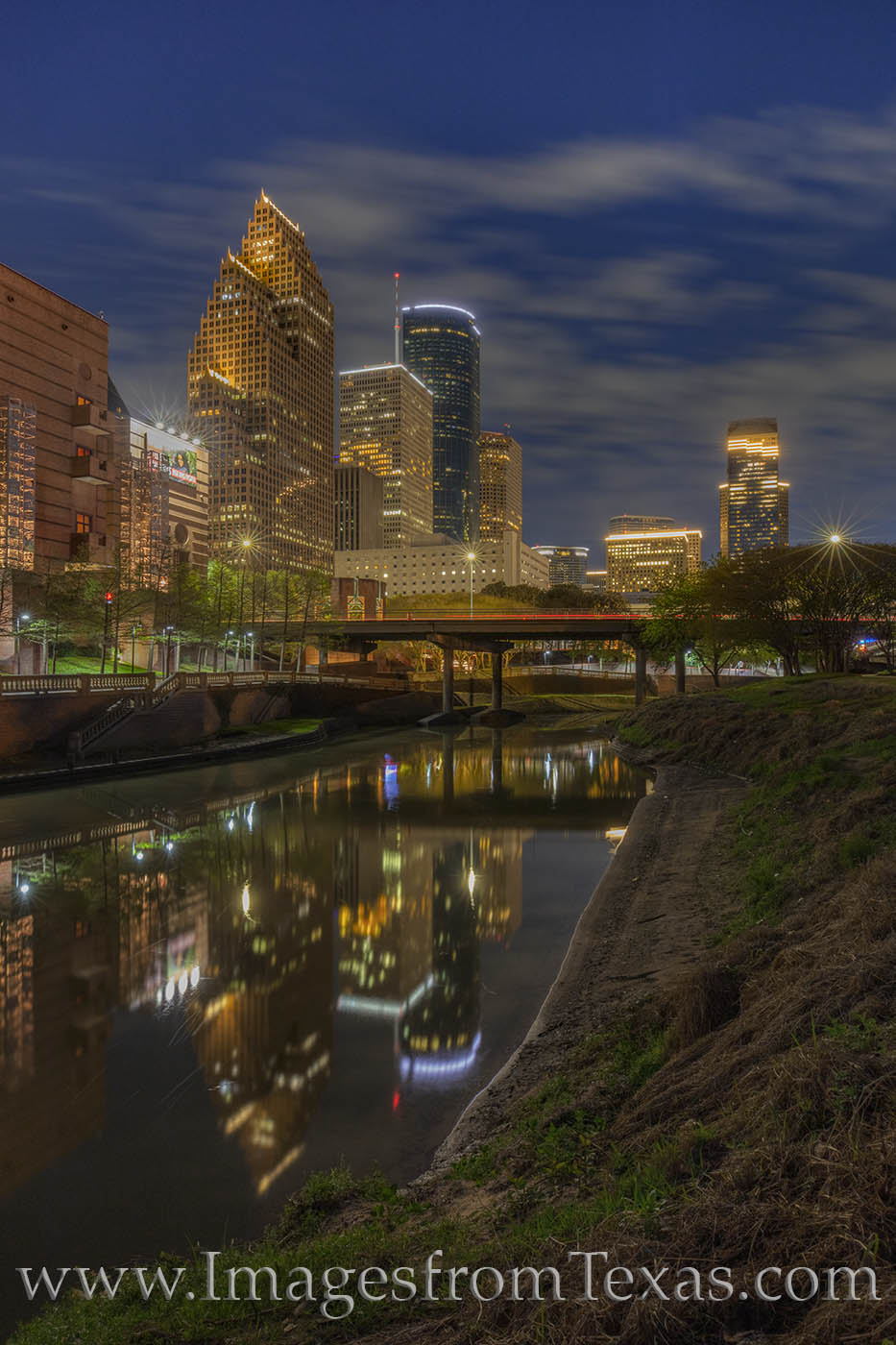 High rises of downtown Houston light up the spring nighttime as their reflections shine in the waters of Buffalo Bayou. The path...