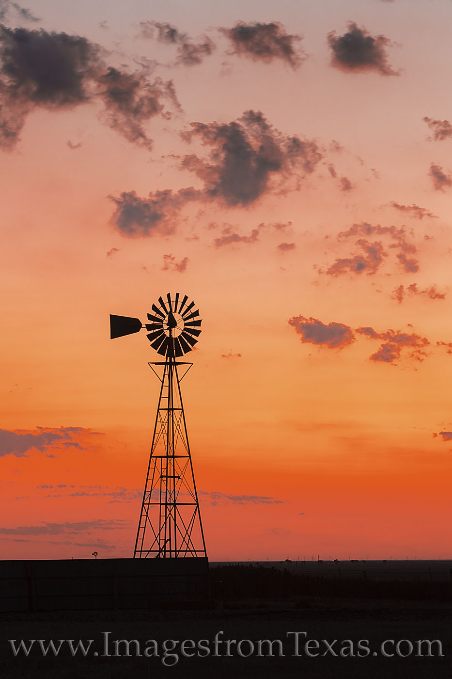 On an unusually cold July morning, a lone windmill stands alone against an orange sky about 20 minutes before sunrise.